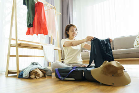Happy young woman hands packing clothes into travel luggage on bed at home or hotel room for a new journey.  Tourism and vacation concept