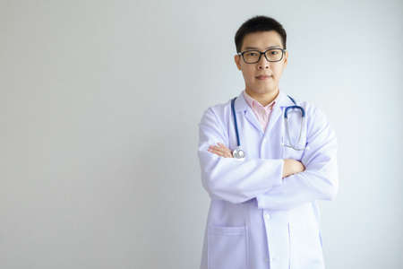 Male asian doctor working in the office hospital wearing face mask protect Covid 19 viruses. Healthcare And Medical concept.