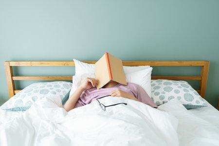 Asian handsome man Read books while sleeping. Man book cover Drowsiness causes sleep.The concept of adequate sleep. Good sleep