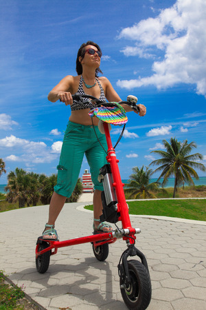 new ages: Woman on on electric tricycle in Miami Stock Photo