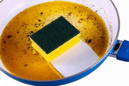 Sponge in a clean frying pan - cutout Stock Photo