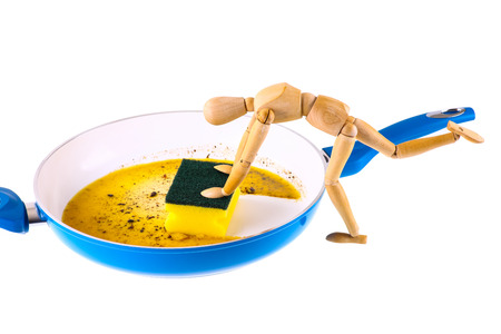 frying pan: Wooden dummy cleans frying pan - isolated