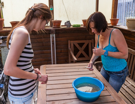 Mother and daughter clean garden furniture
