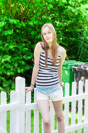 picket fence: Teenage girl at a picket fence Stock Photo