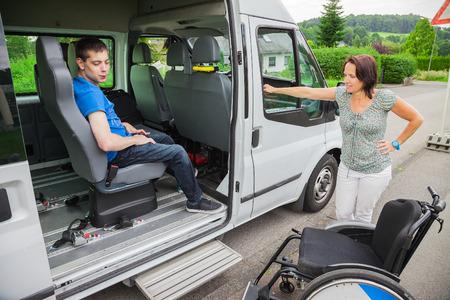 niños discapacitados: Muchacho perjudicado es recogido por el autobús escolar Foto de archivo
