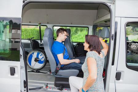 障害を持つ少年、スクールバスによってピックアップします。 写真素材