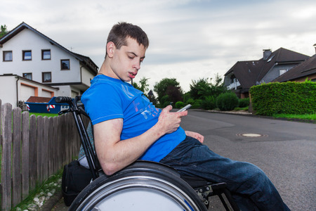 school year: Handicapped boy with smartphone waiting for the school bus Stock Photo