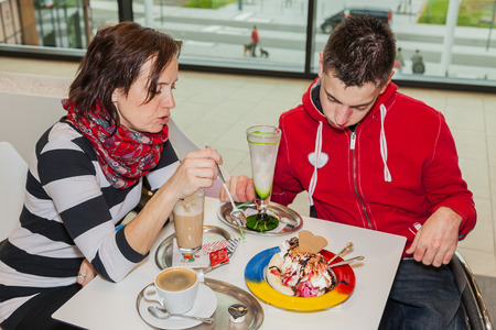 parlor: Mother with handicapped son in an ice cream parlor Stock Photo