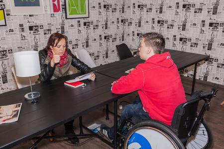 A teacher explains a handicapped boy a lesson.