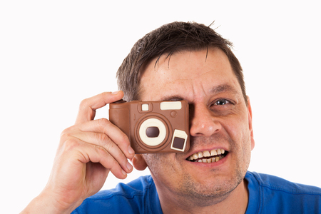 model home: A man photographed with a camera made of chocolate - isolated