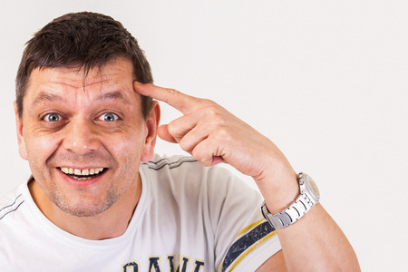animal idiot: A man shows: youre not right in the brain, you have a screw loose - isolated Stock Photo