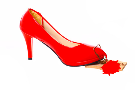 bloodied: Bleeding Red High Heel in a mousetrap. Stock Photo