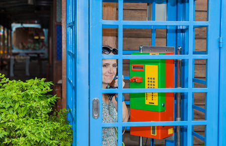 phonebooth: A woman phoned in a colorful phone booth. Stock Photo