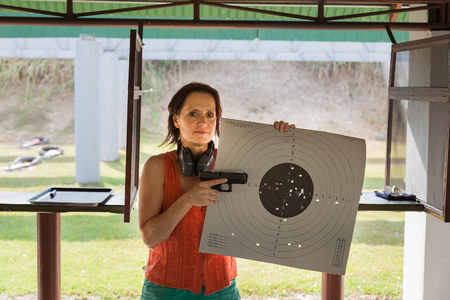 A woman at a shooting range with gun and target Foto de archivo