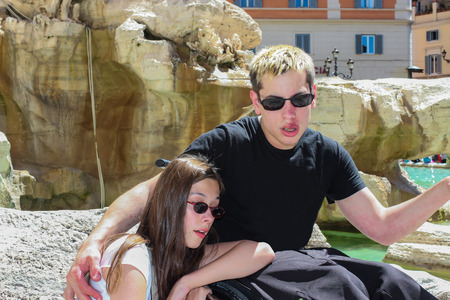invalidity: Teenage girl with handicapped boyfriend in front of the Trevi Fountain in Rome.