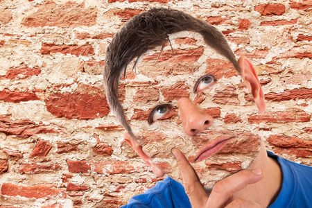camouflaged: Camouflage -man camouflaged in front of a wall Stock Photo