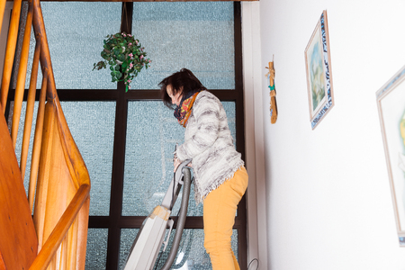 stairwell: Woman vacuuming in an old stairwell