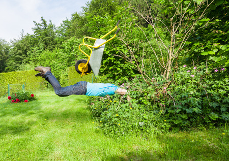 fallacy: Man flies with wheelbarrow in a bush. Stock Photo