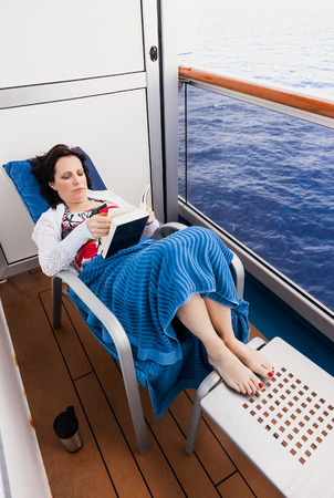 stateroom: Woman on the balcony of a cruise ship.