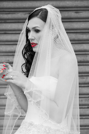 Black and white image of a bride with red lips and red nails