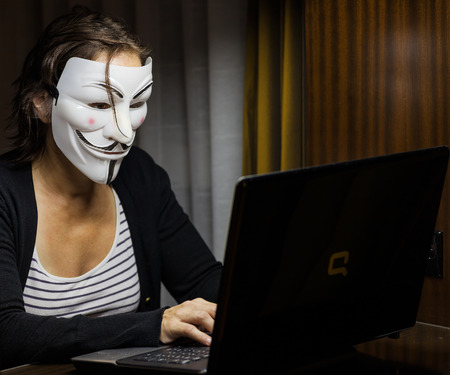 anonymity: Pattaya, Thailand – November 17, 2015: A woman with Vendetta mask in front of a laptop. This mask is a well-known symbol for the online hacktivist group Anonymous. Also used by protesters. Editorial