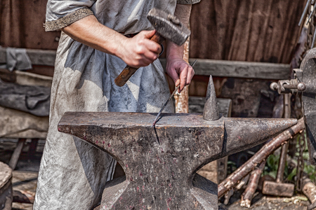 Medieval blacksmith at work with hammer and anvil.