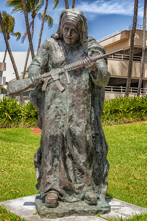 Miami, USA - April 10, 2014: This large bronze statue of Mother Teresa is one of nine works in Bayfront Park for Art Basel. The exhibit titled WAR to WAR features historical figures, known for their humanitarian, work holding guns. The statues are the wor Editorial