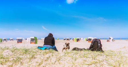 Woman with dog and backpack on a dog beach Stock Photo
