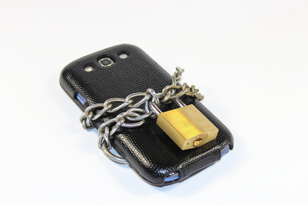 Smartphone locked with a chain and a lock - isolated