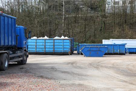 Recyclingwerf met vrachtwagens en containers