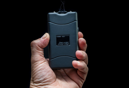 Hand holds a stun gun in front of black background Standard-Bild