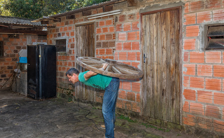 A man carries a wooden wheel on his back. Imagens