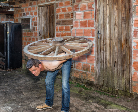 A man carries a wooden wheel on his back. Stock Photo