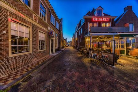 Enkhuizen, The Netherlands - May 04, 2019: Old street in Enkhuizen at the IJsselmeer in the Netherlands during dusk.