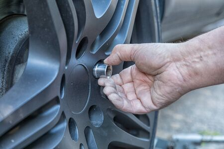 Closeup of a hand attaching a screw to the wheel of a car.