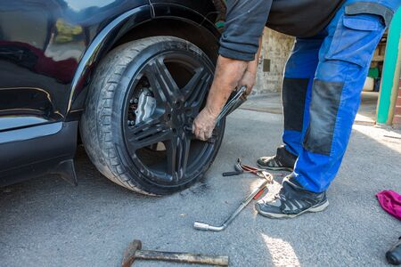 A man changing a wheel on a car. Stock Photo