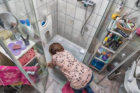 A woman is cleaning a shower cubicle