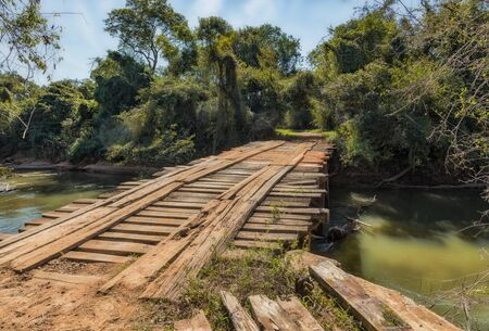Old unsafe wooden bridge without railing in the wilderness of Paraguay. This is used by cars and even tractors.