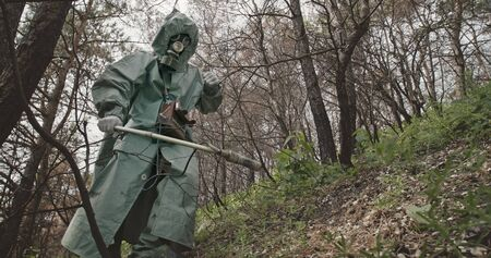 Low angle unrecognizable guy in hazmat suit and gas mask searching for radiation with Geiger counter in abandoned forest near Chernobyl. Stock fotó