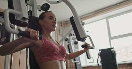 Young, attractive woman using chest press machine - slow motion, medium shot Stock fotó