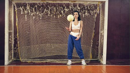 Beautiful girl standing with a soccer ball at the gate in the school gym