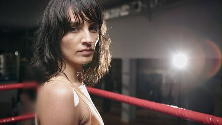 Portrait of a young boxer looking at the camera while practicing in boxing ring Stock Photo