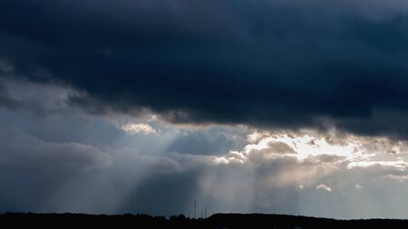 A ray of sunlight breaking through dark clouds.