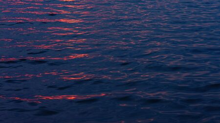 Light waves on the water at night with glare from sunlight. Фото со стока