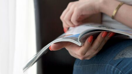 Woman Hands holding open holding magazine. Close up.