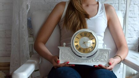 A young girl with art makeup sitting in a white armchair and holding a clock on her knees. Фото со стока