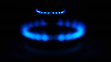 Gas stove with flames over it - on black background.
