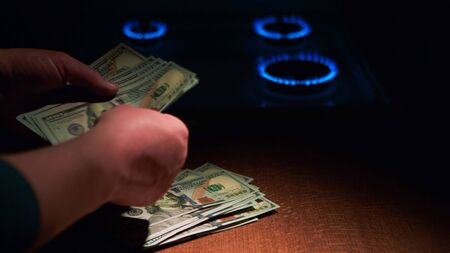 The payment for the spent gas. Man hands ticking money at gas stove. Фото со стока
