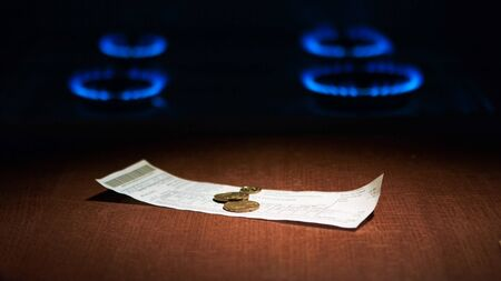 Utility bill and coins for payment against the backdrop of burning gas on gas stove.