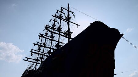 The silhouette of a large wooden ship with mast and sail against the sky.
